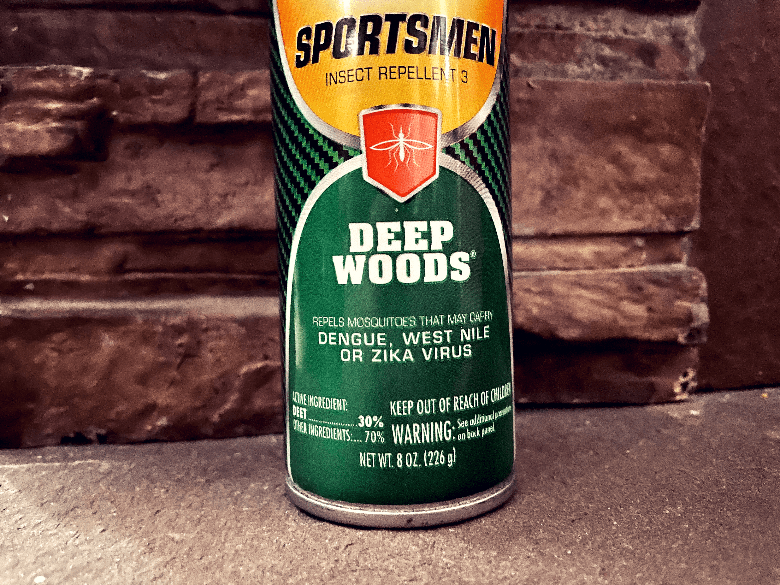 Bottle of DEET bug spray sitting against a fireplace.