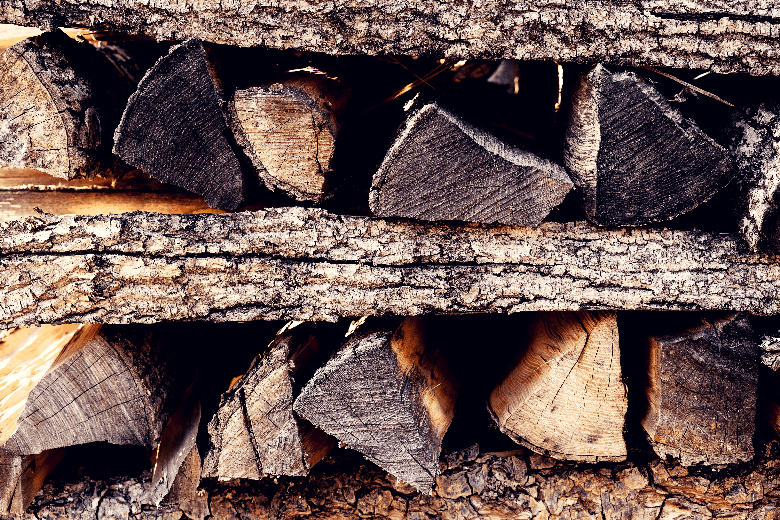 Group of large, triangular-shaped logs stacked on top of each other horizontally.