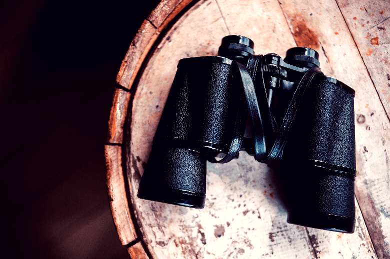 A pair of black binoculars sitting face down on the top of a barrel.