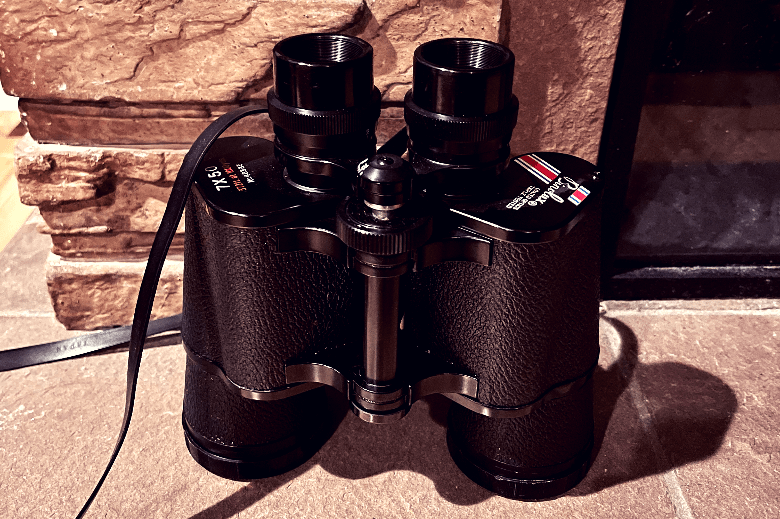 Black binoculars sitting at the edge of a fireplace with its objective lenses facing down.