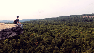 Mike sitting at the edge of a cliff overhanging over a vast forest.