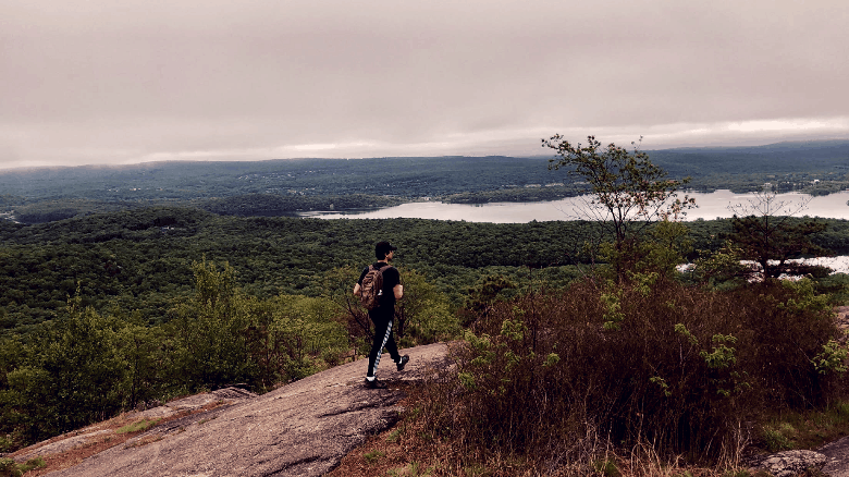 Mike walking across a tilted mountain top with lots of trees and a reservoir in the distance.