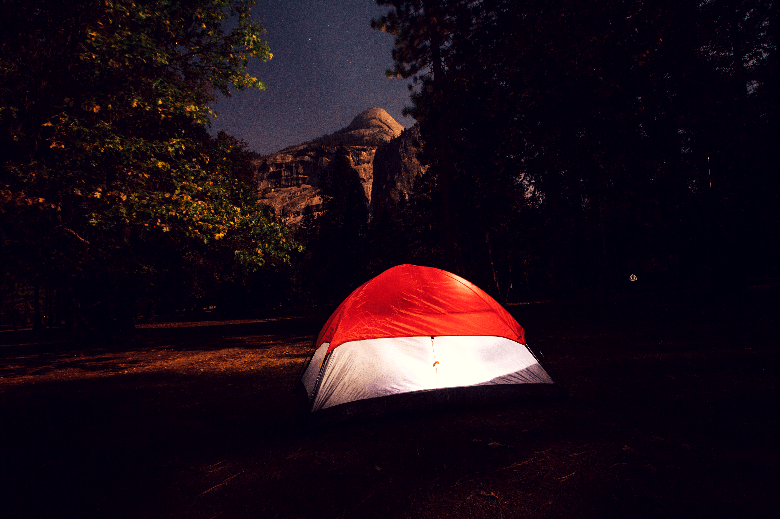 Dome tent sitting in a field with a light on at night.