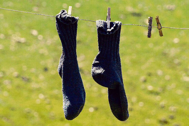 Pair of dark-colored socks hanging from a clothes line.