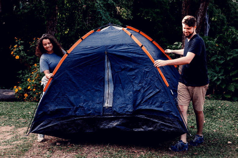 Two people picking up and happily carrying a tent.