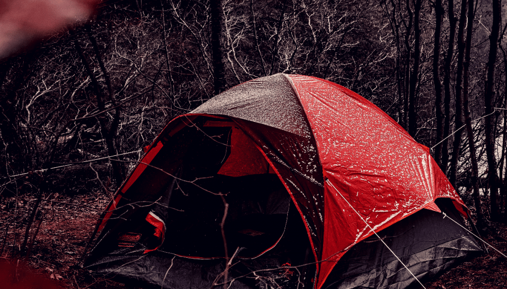 Tent covered with droplets of water sitting in a shaded area.