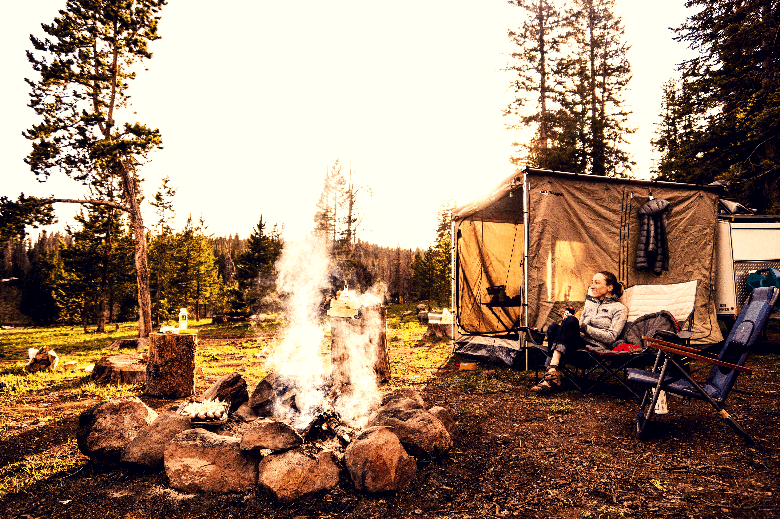 Campfire set up near a cubical-looking tent.