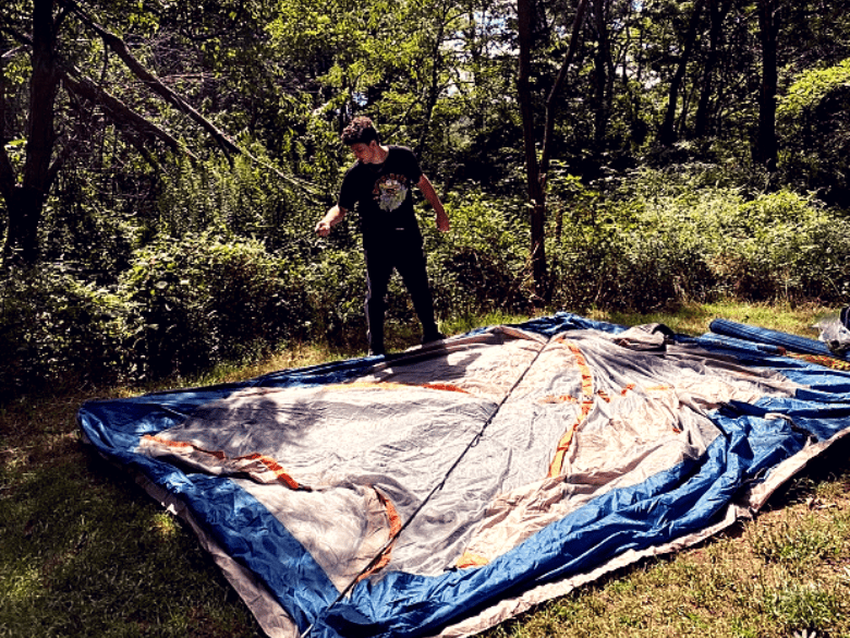 Mike setting up a tent on a flat area of land in the woods.