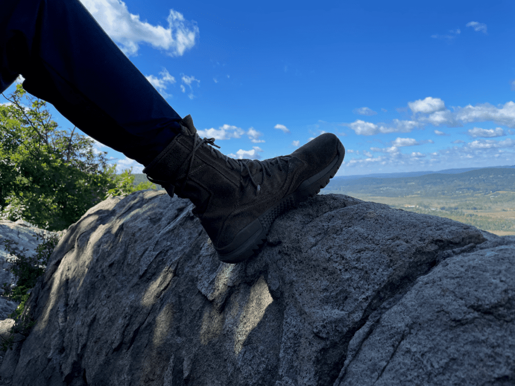 Blue pant leg and boot resting on the edge of a cliff.